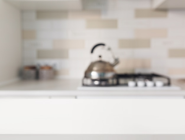 Empty white table in front of blurred kitchen counter