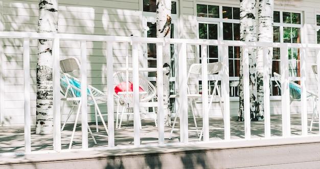 屋外の歩道通りにある色付きの枕とレストランのカフェの椅子の外の空の白いテーブル