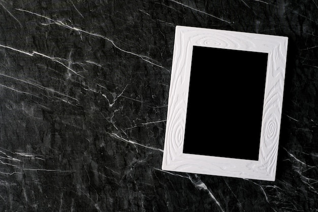 Empty white vintage wooden frame on black marble  background