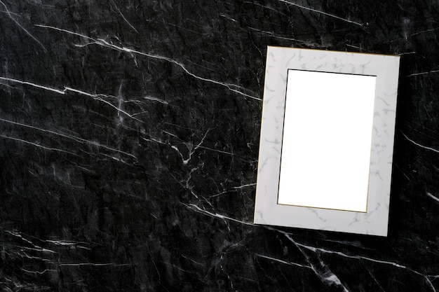 Empty white vintage wooden frame standing over white cement wall and black marble floor with shadow background, copy space for mock up and template
