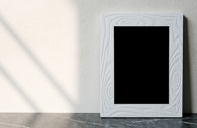 Empty white vintage wooden frame standing over white cement wall and black marble floor with shadow background