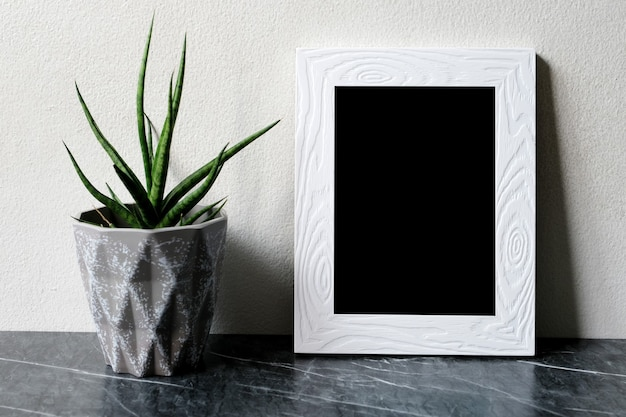 Empty white vintage wooden frame standing over white cement wall and black marble floor with shadow