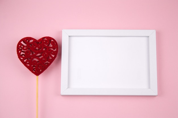 Empty white wooden frame and red heart on a pastel pink background