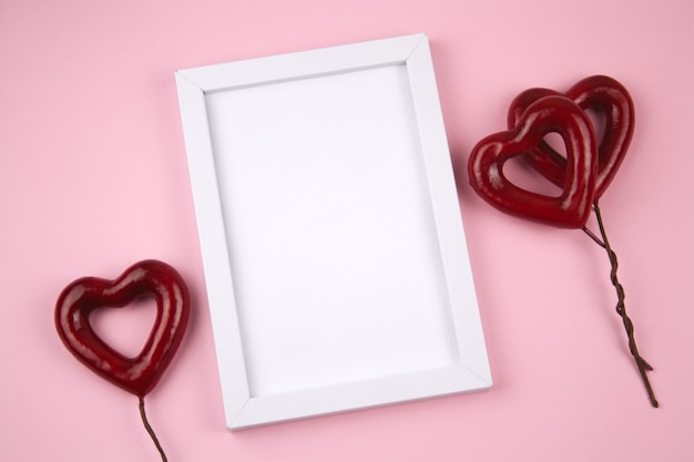Empty white wooden frame and red hearts on a pastel pink background