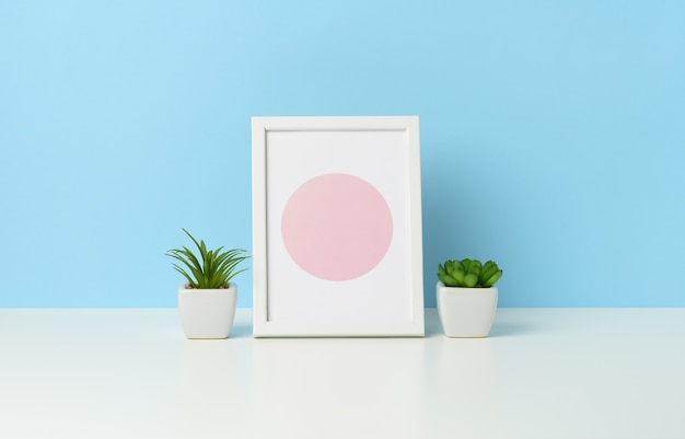 Empty white wooden photo frame and flowerpots with plants on white table, blue background