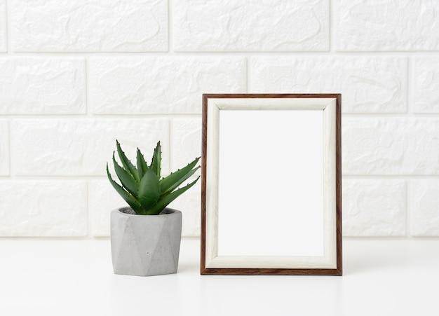 Empty white wooden photo frame and flowerpots with plants on white table, white background