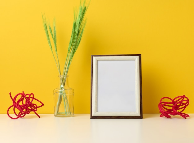 Empty white wooden photo frame and green plants on white table, yellow background