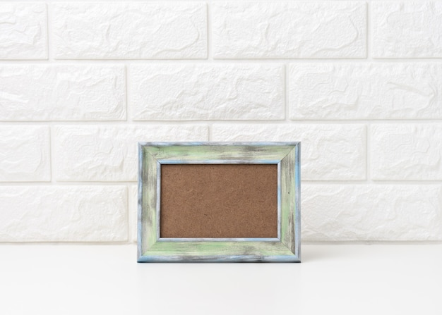 Empty white wooden photo frame on white table, white background, minimalism in the interior