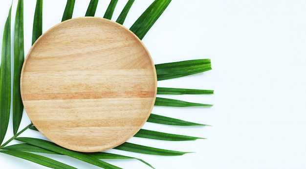 Empty white wooden plate on tropical palm leaves on white background.