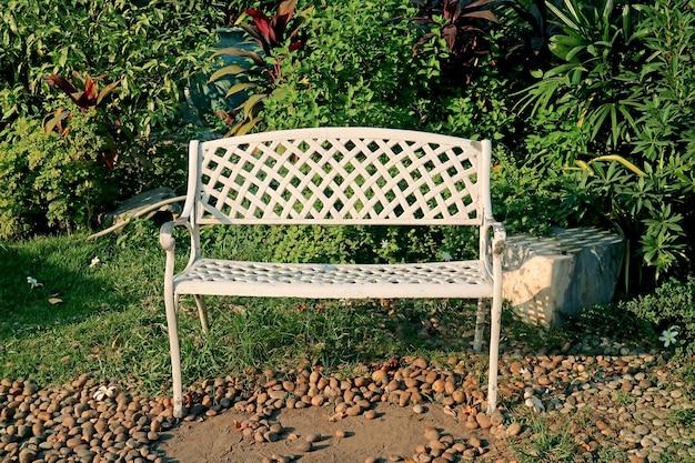 Empty white wrought iron bench in the sunshine garden