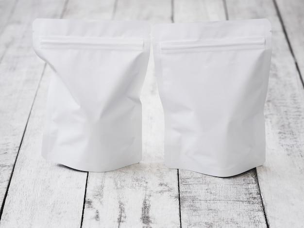 Опорожните белый пакет почтового индекса для еды на винтажном деревянном столе.