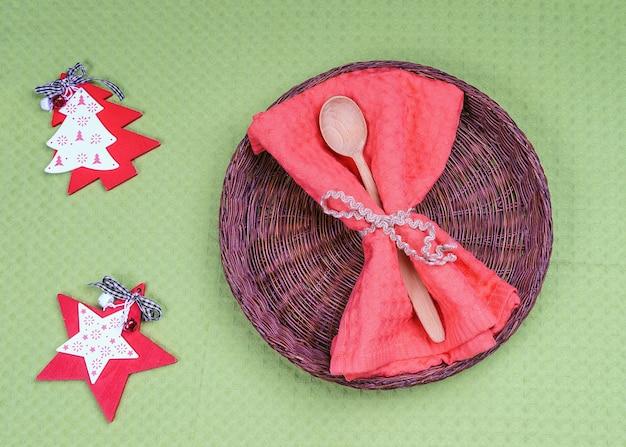Пустая плетеная тарелка и деревянная ложка с украшением рождества и нового года для праздничного меню.