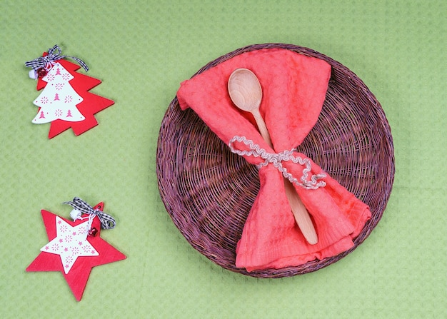 Empty wicker plate and wooden spoon with christmas and new year decoration for holiday menu.