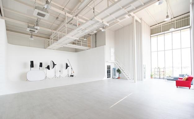 Пустая широкая и высокая крытая мастерская фотостудии промышленного дизайна, полная пространства и профессионального фотографического оборудования, размещенного на белой стене и полу, с лампочками и кондиционером.