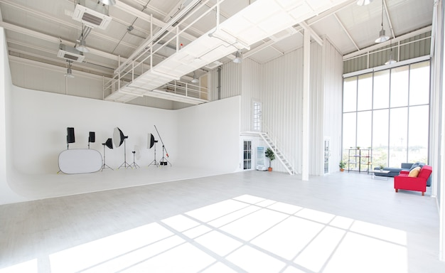Пустой, широкий и высокий новый чистый промышленный архитектурный дизайн для профессиональной фотографии в помещении для студии в классе, с высокими стеклянными окнами со вспышкой, штативом, подставкой, отражателем.