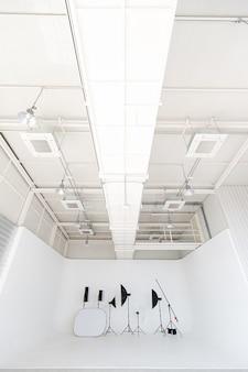 Пустые, широкие и высокие новые чистые профессиональные фотостудии в помещении для студийного освещения.