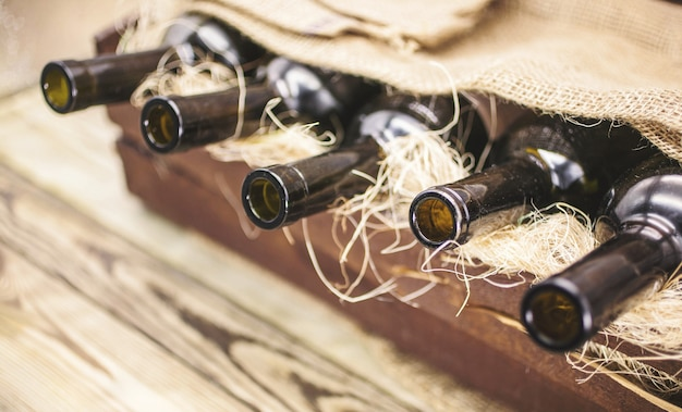 Empty wine bottles in a wooden box on a rustic table.