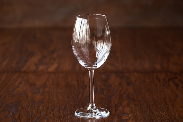Empty wine glass on the dark wooden table