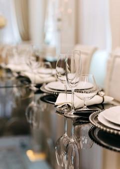 レストランのテーブルに空のワイングラスとプレートの配置