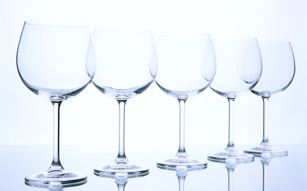 Empty wine glasses arranged andd on white
