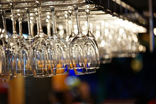 Empty wine glasses hanging on bar rack with bokeh background