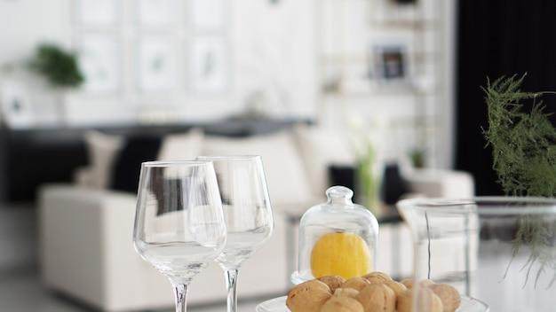 モダンなインテリアのぼやけた背景に空のワイングラス。ホテルや家の部屋の黒と白のインテリア。