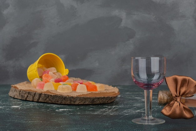 Bicchiere di vino vuoto con secchio giallo di caramelle di gelatina.