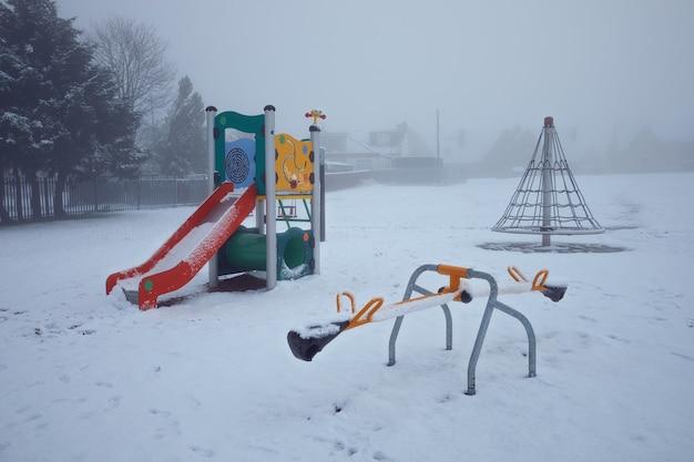 雪に覆われた空の冬のカラフルな遊び場ウェストロージアンスコットランドイギリス