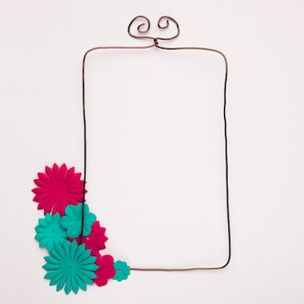 Empty wired frame decorated with handmade blue and pink flowers on white backdrop