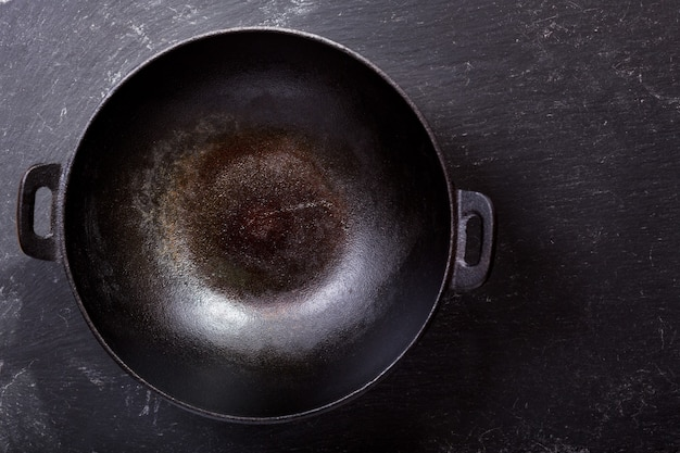 Empty wok pan on a dark table, top view