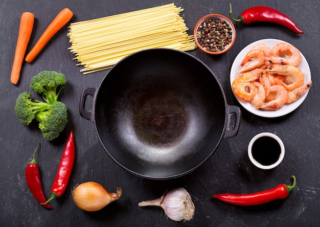 Empty wok pan with ingredients for cooking stir fried noodles with shrimps on a dark table, top view