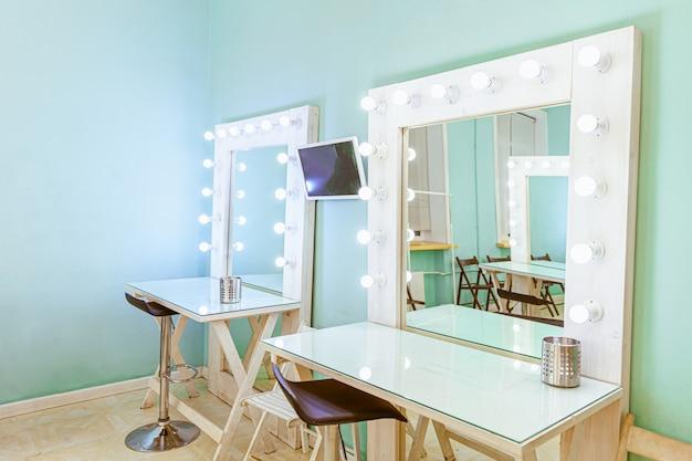 鏡と電球が付いている空の女性の化粧ステーション