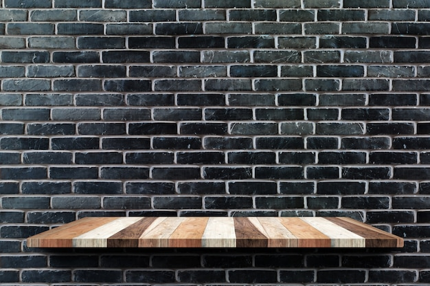 Empty wood board shelf at black brick wall background