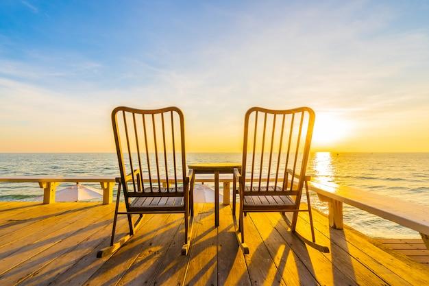 아름다운 열대 해변과 바다와 야외 테라스에서 빈 나무 의자와 테이블