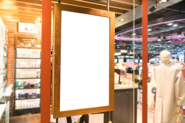 Empty wood frame poster display on glass window at shop storefront