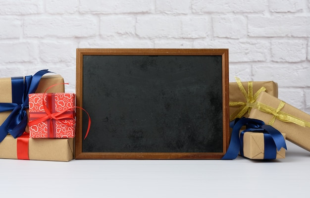 Empty wood frame and stack of various gift boxes on white brick background, festive backdrop
