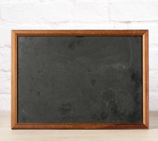 Пустая деревянная рамка с черным, за белой кирпичной стеной