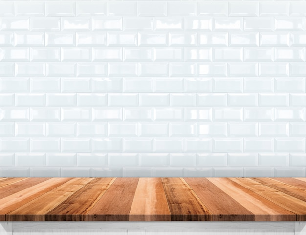 Empty wood plank table top with glossy ceramic white tile wall background