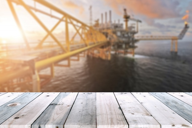 Empty wood plank table with oil and gas platform or construction platform offshore rig blur background for presentation and advertorial.