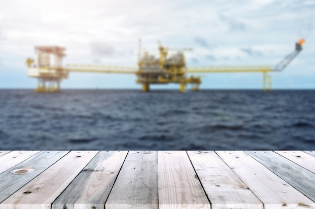 Empty wood plank table with oil and gas platform or construction platform offshore rig blur background.