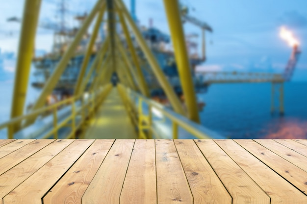 Empty wood plank table with oil and gas platform or construction platform offshore rig blur background