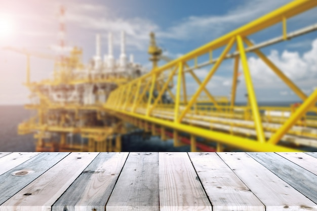 Empty wood plank table with oil and gas platform