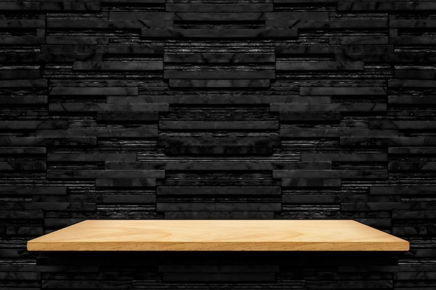 Empty wood shelf at black layer marble tile wall background