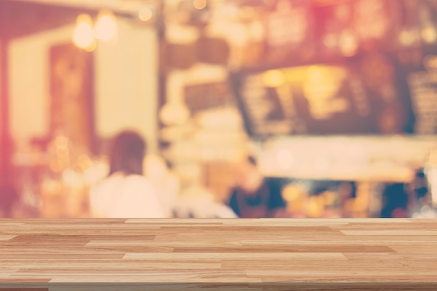 Пустой стол древесины и размытый фон дисплей в кафе с местом для продукта.