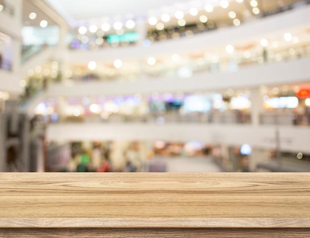 空の木製テーブルとぼんやりとした百貨店の背景。製品表示テンプレート