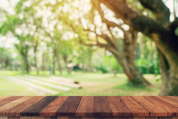 空の木のテーブルと日光の下で庭の木のぼやけた緑。製品のモンタージュを表示します。