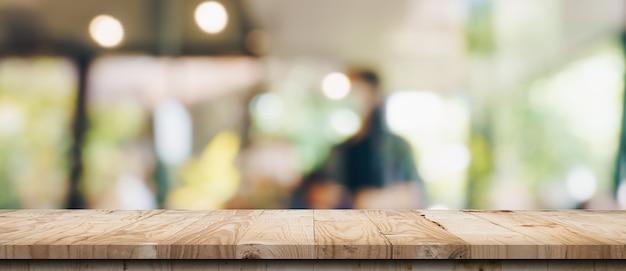 Пустой деревянный стол и размытый светлый стол в кафе и кафе с фоном боке. шаблон отображения товара.