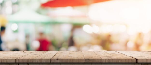 ボケ味の背景を持つショッピングモールの空の木製テーブルとぼやけたライトテーブル。製品表示テンプレート。