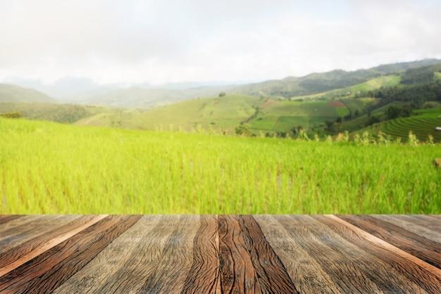 空の木製テーブルとぼやけた田んぼと朝の山の風景。