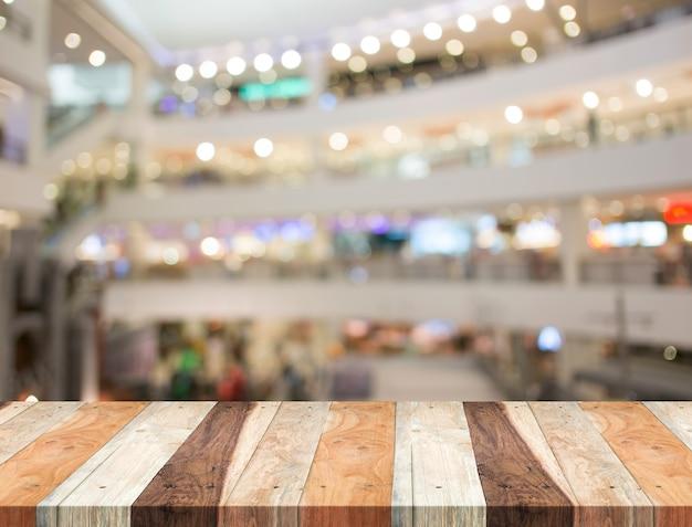 空の木製テーブルとぼんやりしたショッピングモールの背景。製品の表示テンプレート。ビジネスプレゼンテーション